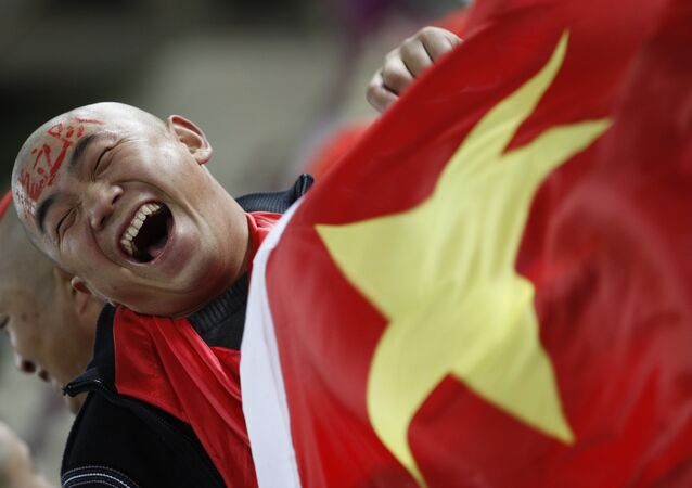 In this Wednesday, Jan. 12, 2011, file photo, a Chinese soccer fan cheers for his team before their AFC Asian Cup group A soccer match against Qatar in Doha, Qatar.