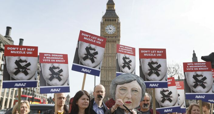 Demonstrators, one dressed in a Theresa May puppet head pose near parliament in London