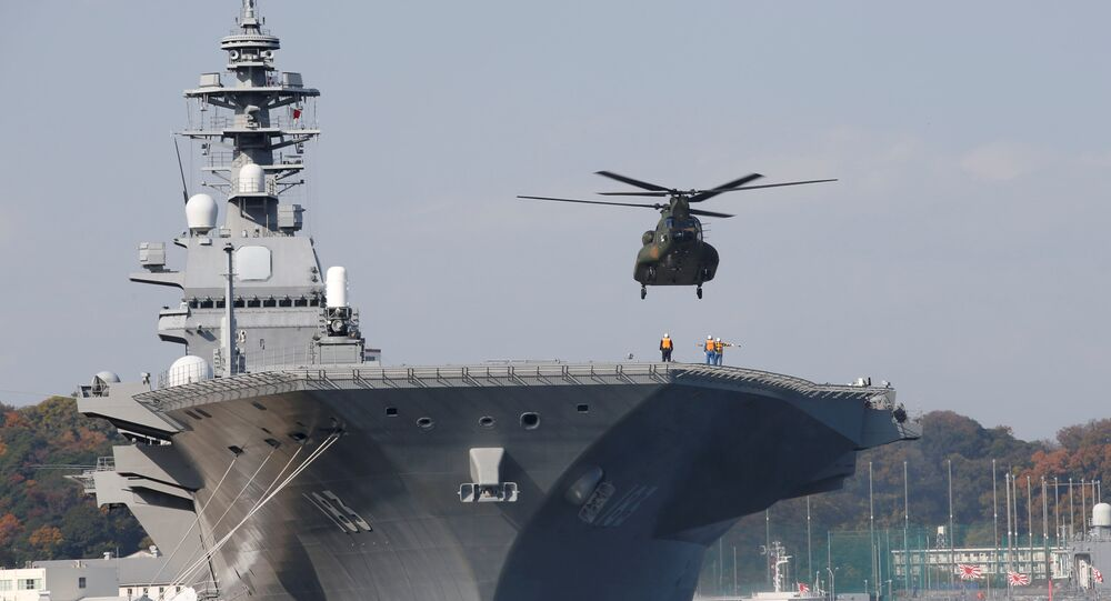 A helicopter lands on the Izumo, Japan Maritime Self Defense Force's (JMSDF) helicopter carrier, at JMSDF Yokosuka base in Yokosuka