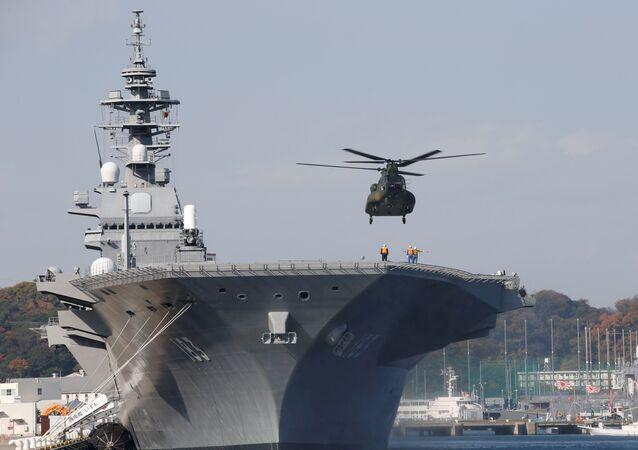 A helicopter lands on the Izumo, Japan Maritime Self Defense Force's (JMSDF) helicopter carrier, at JMSDF Yokosuka base in Yokosuka