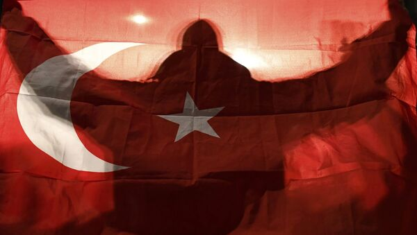 A demonstrator holds a Turkish flag outside the Turkish consulate in Rotterdam where a crowd gathered to await the arrival of the Turkish Family Minister Fatma Betul Sayan Kaya, who decided to travel to Rotterdam by land after Turkish Foreign Minister Mevlut Cavusoglu's flight was barred from landing by the Dutch government, in Rotterdam, Netherlands March 11, 2017. - Sputnik International
