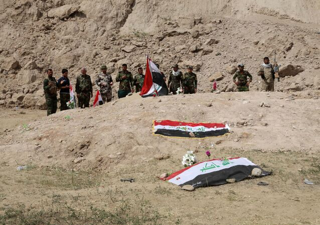 Iraqi security forces and allied Shiite militiamen pray at the site of a mass grave (file)