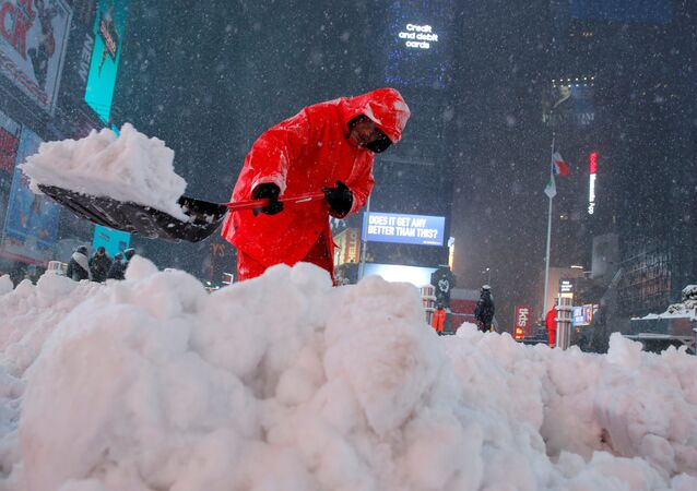 A worker clears snow in Times Square as snow falls in Manhattan, New York, U.S.