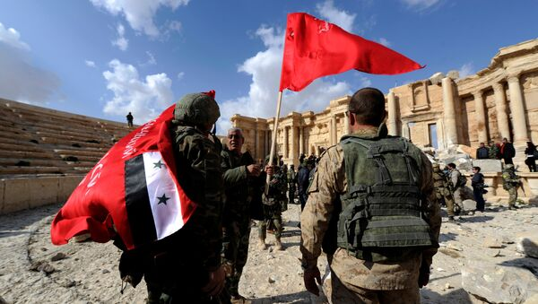 Syrian army soldiers carry flags in the amphitheater of the historic city of Palmyra, Syria March 4, 2017. - Sputnik International