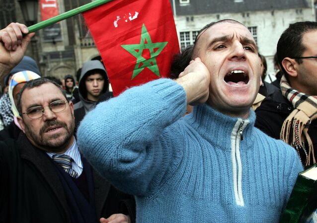 Demonstrators wave a  Moroccan flag during at Dam Square in Amsterdam, the Netherlands, Saturday, Feb, 11, 2006.
