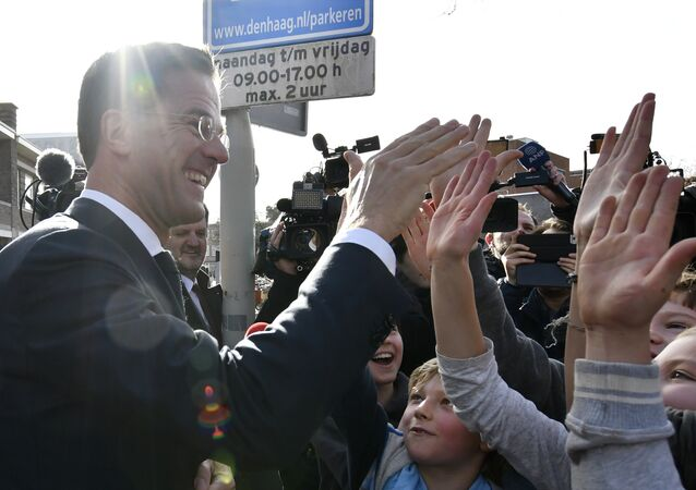 Dutch Prime Minister Mark Rutte gives 'high five' to children after casting his vote for the Dutch general election in The Hague, Netherlands, Wednesday, March 15, 2017