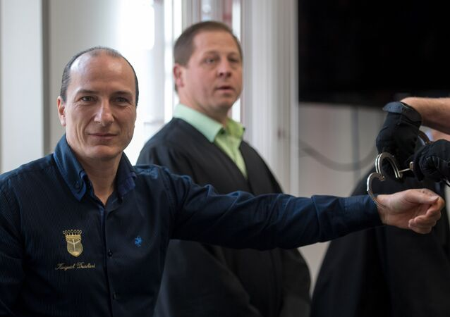Self-appointed King of Germany Peter Fitzek (L) is taken off the handcuffs as he arrives for his trial at court in Halle/Saale, central Germany, on March 15, 2017