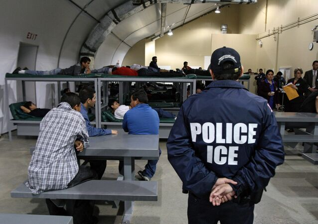 An Immigration and Customs Enforcement (ICE) officer guards a group of 116 Salvadorean immigrants that wait to be deported,at Willacy Detention facility in Raymondville, Texas on 18 December 2008
