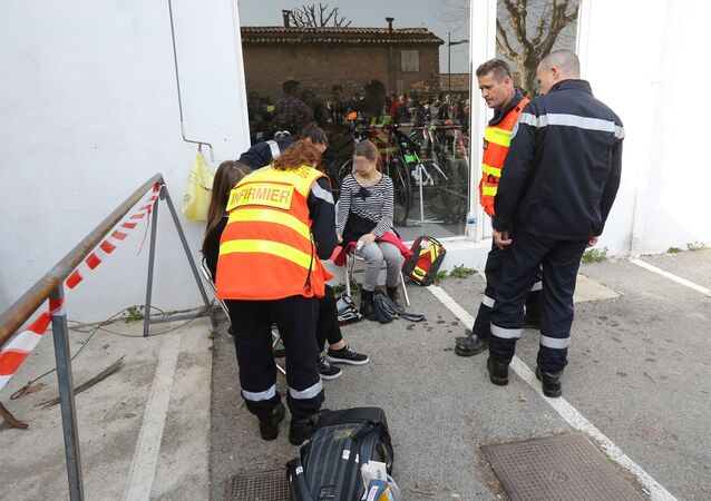 Firefighters give assistance to people near the Tocqueville high school in the southern French town of Grasse, on March 16, 2017 following a shooting that left eight people injured