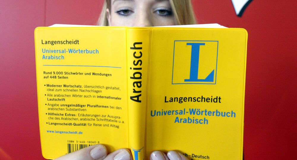 A young woman holds an universal dictionary Arabic as she sits in front of a poster at the International Bookfair in Frankfurt , Germany (File)
