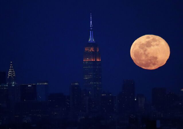 The full moon rises behind the New York City skyline, including the Empire State Building, centre, and the Chrysler Building, left, as seen from downtown Newark, NJ, Sunday, 12 March 2017.