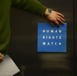 A man puts a logo of US-based rights group Human Rights Watch on the wall as he prepares the room before their press conference to release their annual World report on January 21, 2014 in Berlin