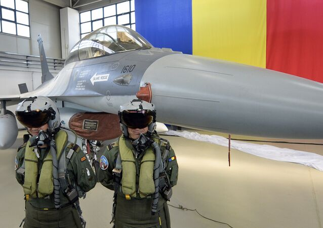 Romanian pilots stand next to a Romanian Air Force F16 fighter jet parked inside a hangar of the Air Base 86, in Borcea, southern Romania, Friday, Oct. 7, 2016.