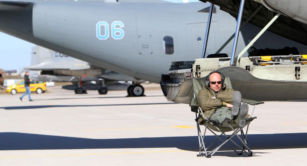 A technician sits near Sweden's C130 Hercules transport aircraft during the Lithuanian - NATO air force exercise at the air force base near Siauliai Zuokniai, Lithunaia on April 1, 2014