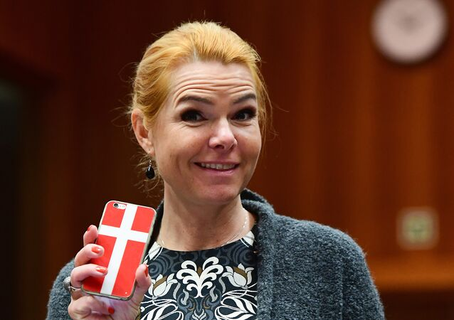 Danish Interior Minister Inger Stojberg holds her phone showing a Danish flags as she attends a Justice and Home Affairs Council at the European Council in Brussels on November 18, 2016