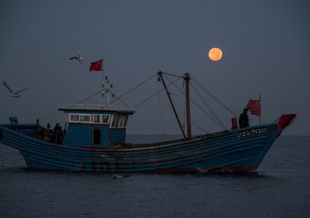 September 17, 2016 shows fisherman on their boat in front of the full moon in Xianrendao in China's northeastern Liaoning province