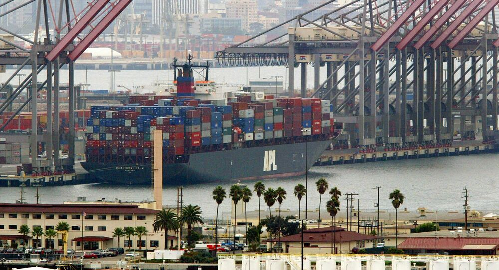 An American President Lines ship loaded with containers is moored next to idle cranes at the Port of Long Beach (File)