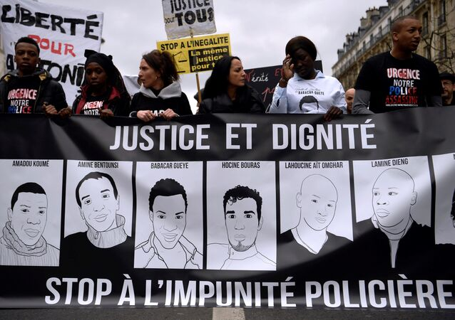 People hold a banner depicting victims of alleged police brutality as they take part in a demonstration called by the families of the victims, LDH, the Mrap, CGT and FSU against police brutality, discrimination and racism in Paris on March 19, 2017