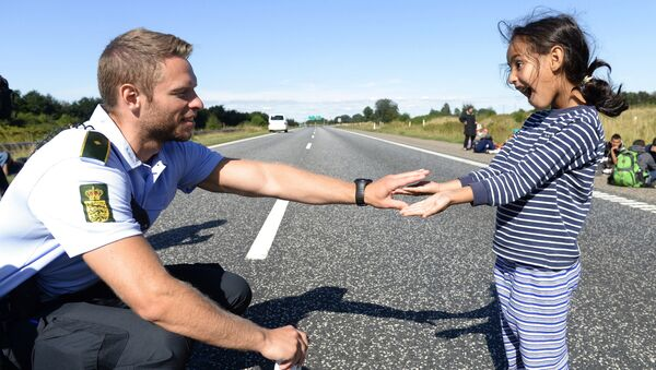 Danish policeman plays with a migrant girl (file) - Sputnik International