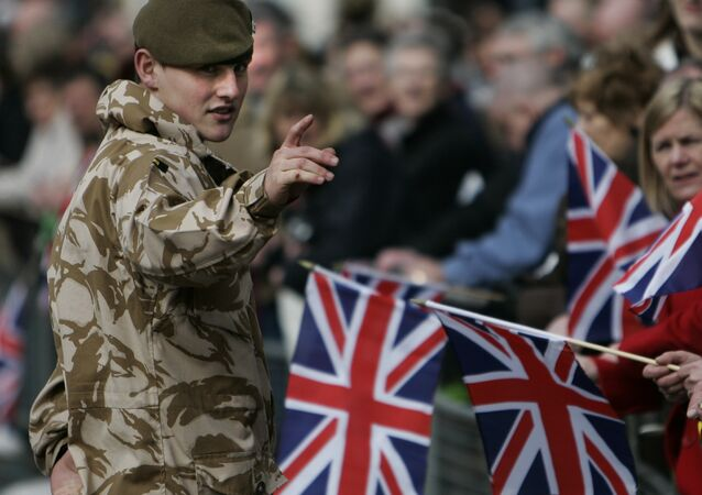 A British soldier from the 2nd Battalion, The Royal Anglian Regiment, talks to people prior to their parade through the town of Watford, England, Wednesday March 11, 2009.
