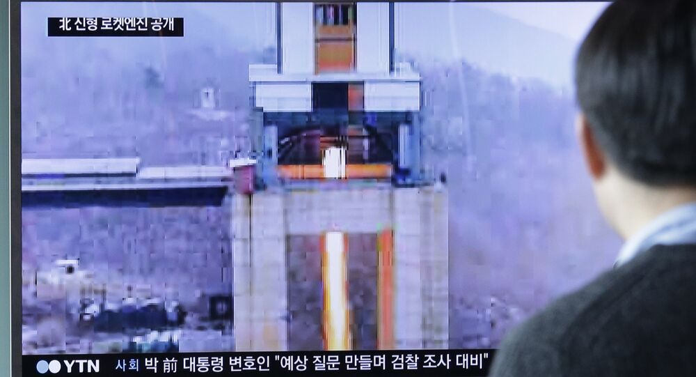 A man watches a TV news program showing an image that North Korea's Rodong Sinmun newspaper reports of a ground test of a new type of high-thrust rocket engine