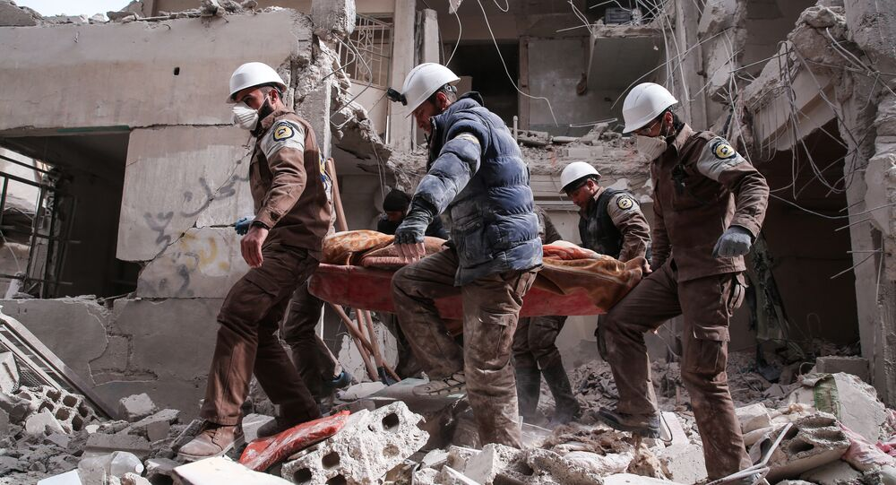 Syrian civil defence volunteers, known as the White Helmets, search for survivors following reported government airstrike on the rebel-held neighbourhood of Tishrin, on the northeastern outskirts of the capital Damascus