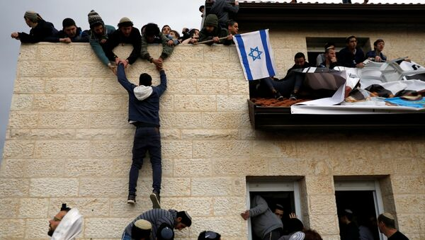 A pro-settlement activist climbs onto a rooftop of a house to resist evacuation of some houses in the settlement of Ofra in the occupied West Bank, during an operation by Israeli forces to evict the houses, February 28, 2017. - Sputnik International