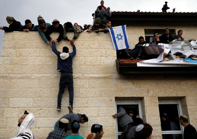 A pro-settlement activist climbs onto a rooftop of a house to resist evacuation of some houses in the settlement of Ofra in the occupied West Bank, during an operation by Israeli forces to evict the houses, February 28, 2017.