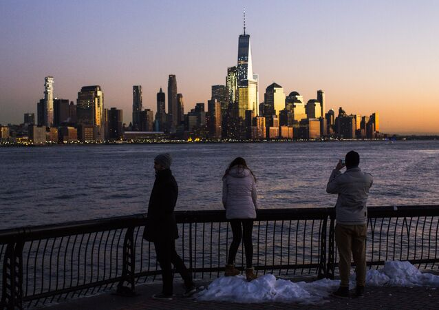 People in Hoboken, New Jersey view lower Manhattan and One World Trade Center in New York City during sunset
