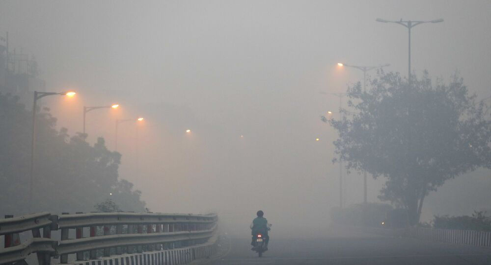 A man rides a scooter on a road enveloped by smoke and smog, on the morning following the Diwali festival in New Delhi, India, 31 October 2016.