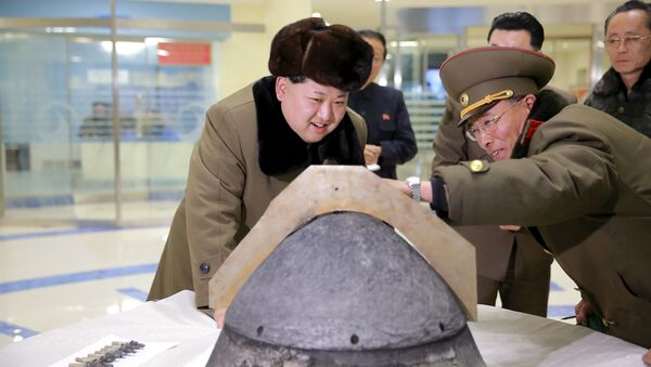 North Korean leader Kim Jong Un looks at a rocket warhead tip after a simulated test of atmospheric re-entry of a ballistic missile, at an unidentified location in this undated file photo released by North Korea's Korean Central News Agency (KCNA) in Pyongyang on March 15, 2016. - Sputnik International