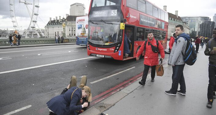 A woman assist an injured person after an incident on Westminster Bridge in London