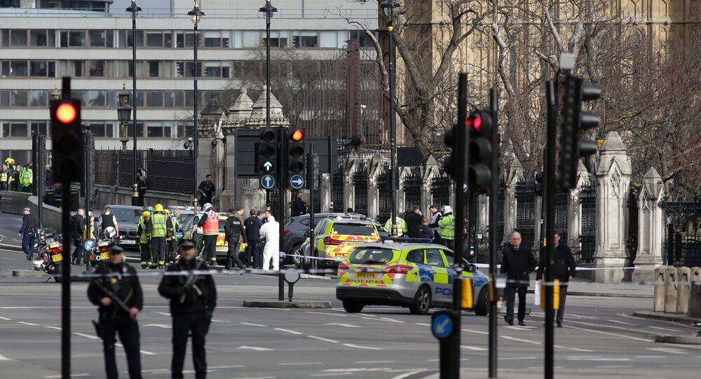 Armed police officers stand guard as forensics officers work around a grey vehicle that crashed into the railings of the Houses of Parliament in central London on March 22, 2017, during an emergency inciden