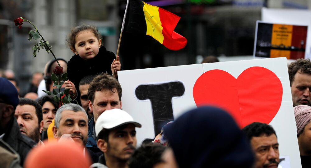 People take part in a march in front of the Brussels Stock Exchange, La Bourse, as part of ceremonies commemorating the first anniversary of twin attacks at Brussels airport and a metro train, Belgium, March 22, 2017.