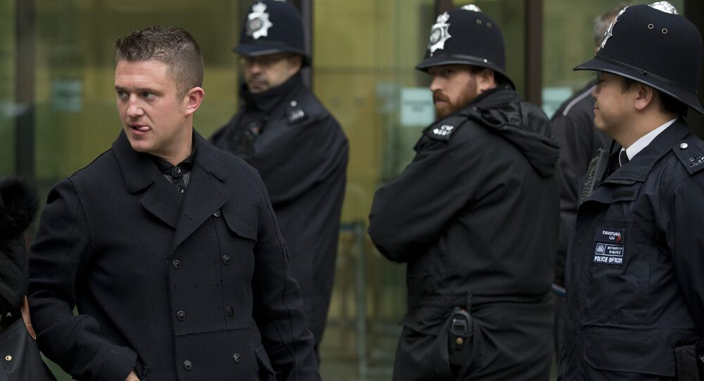 Tommy Robinson, left, the former leader of the far-right EDL English Defence League group walks past police officers as he leaves after an appearance at Westminster Magistrates Court in London, Wednesday, Oct. 16, 2013.