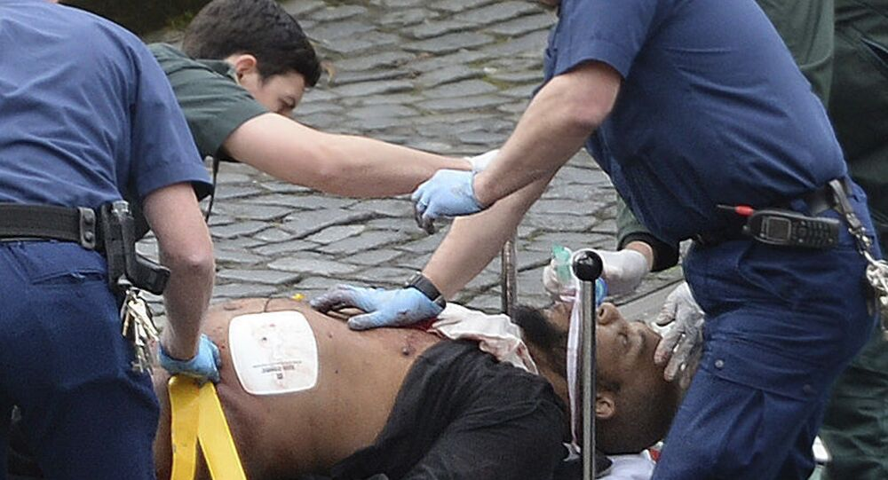 n this March 22, 2017 file photo, the attacker Khalid Masood is treated by emergency services outside the Houses of Parliament London. British Police named on Thursday March 23, 2017, Khalid Masood as The Houses of Parliament attacker.