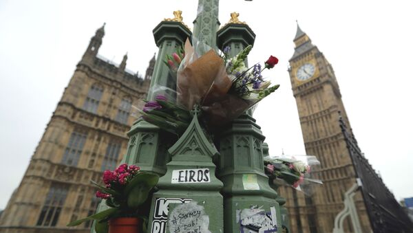 Floral tributes to victims of Wednesday's attack are tied to a lamppost outside the Houses of Parliament in London, Friday March 24, 2017. - Sputnik International