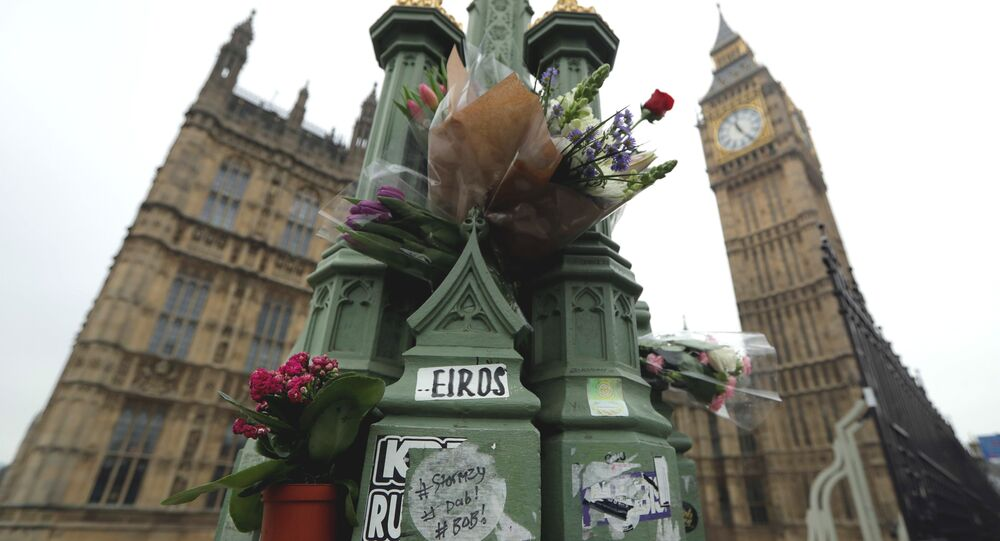 Floral tributes to victims of Wednesday's attack are tied to a lamppost outside the Houses of Parliament in London, Friday March 24, 2017.
