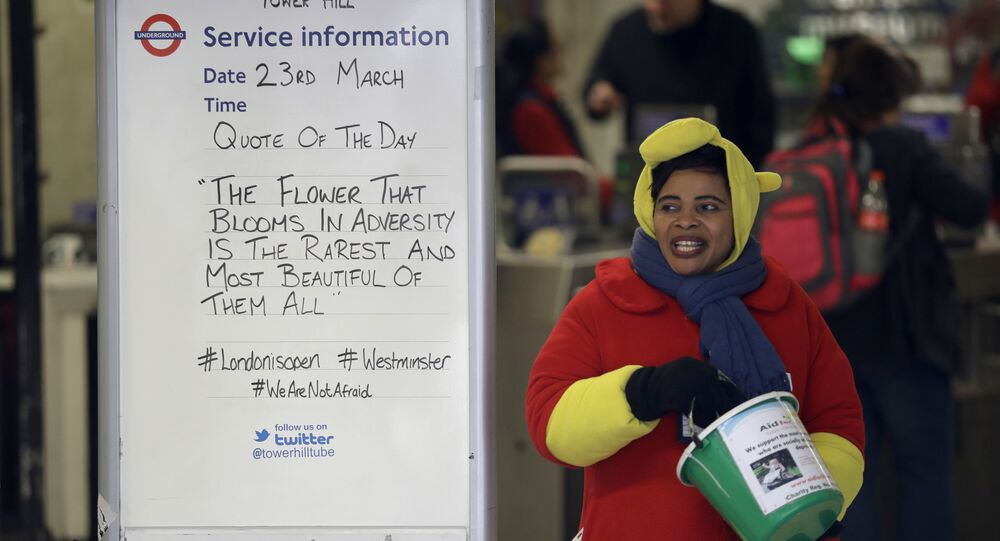 A woman collecting money for charity stands next to a quote written on an information board at Tower Hill underground train station, written in defiance of the previous day's attack in London, Thursday, March 23, 2017.