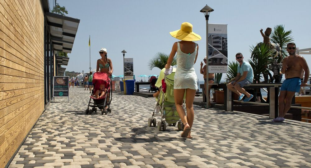 Mothers with baby-strollers walk on the waterfront running along Massandra Beach, Yalta