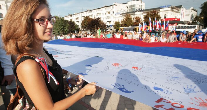 Simferopol residents during the Russian Flag Day celebrations in Crimea. A 162 sq m Russian flag has been spread on the central square in the Crimean capital