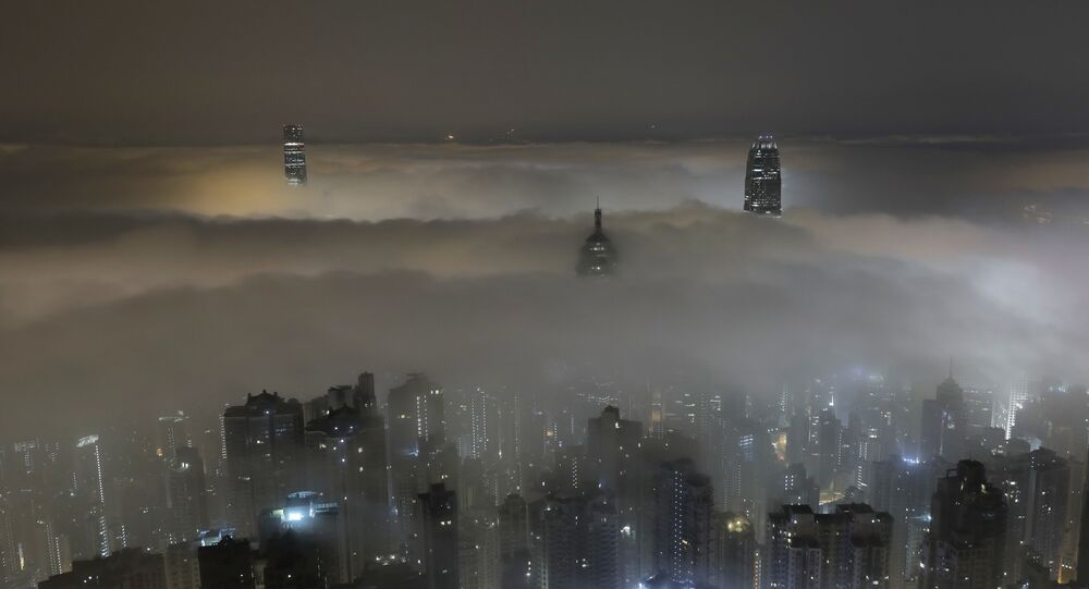 High-rise buildings are partly covered by heavy fog at Hong Kong's Victoria Harbour Monday, March 20, 2017.
