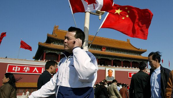 A man walks past flags of Canada and China in front of Tiananmen Gate in Beijing (File) - Sputnik International