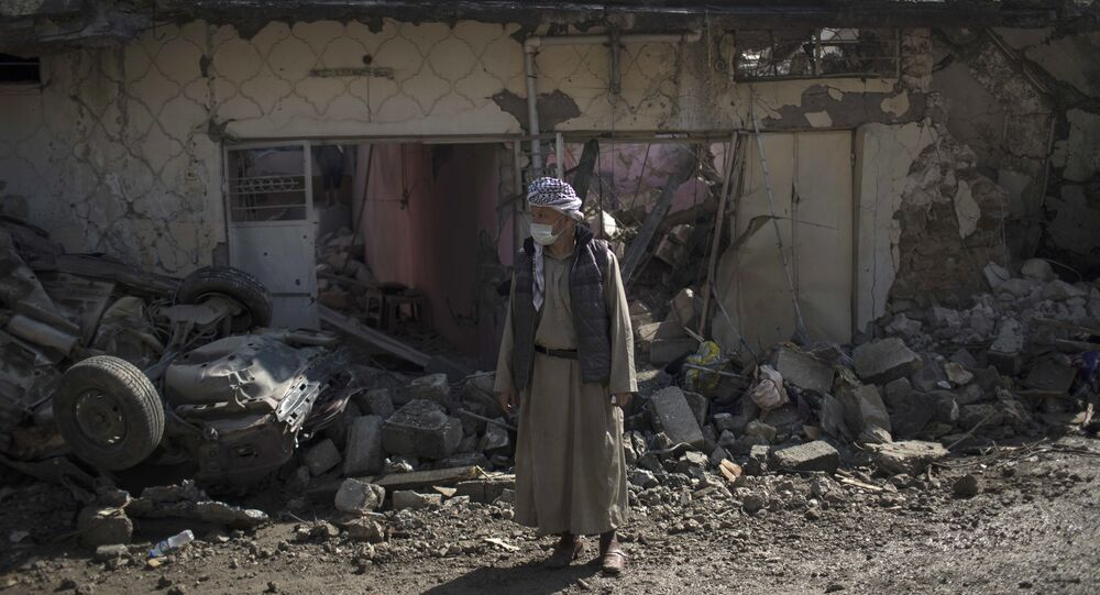 A man stands outside houses damaged during fights between Iraq security forces and Islamic State on the western side of Mosul, Iraq, Friday, March 24, 2017.