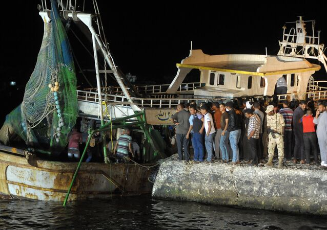 This file photo taken on September 28, 2016 shows people gathering on the quay as a wreck of a migrant boat raised by the Egyptian navy and maritime rescuers arrives in the Egyptian port city of Rosetta. An Egyptian court on March 26, 2017 sentenced 56 people to prison terms of between seven and 10 years over the deaths at sea of at least 202 migrants in September, judicial officials said