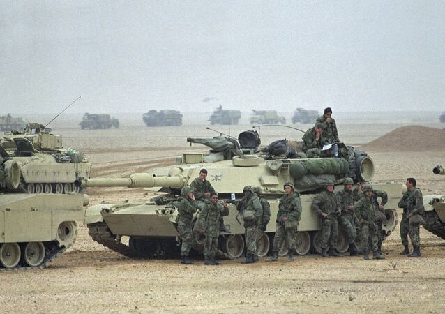 Troops from the Army's 1st Infantry Division lean on an M1A1 Abrams main battle tank as a convoy passes in the background at an assembly point in afternoon on Sunday, Jan. 21, 1991 in Saudi Arabia. Troops from the 1st Infantry Division have taken up positions close to the border with Kuwait