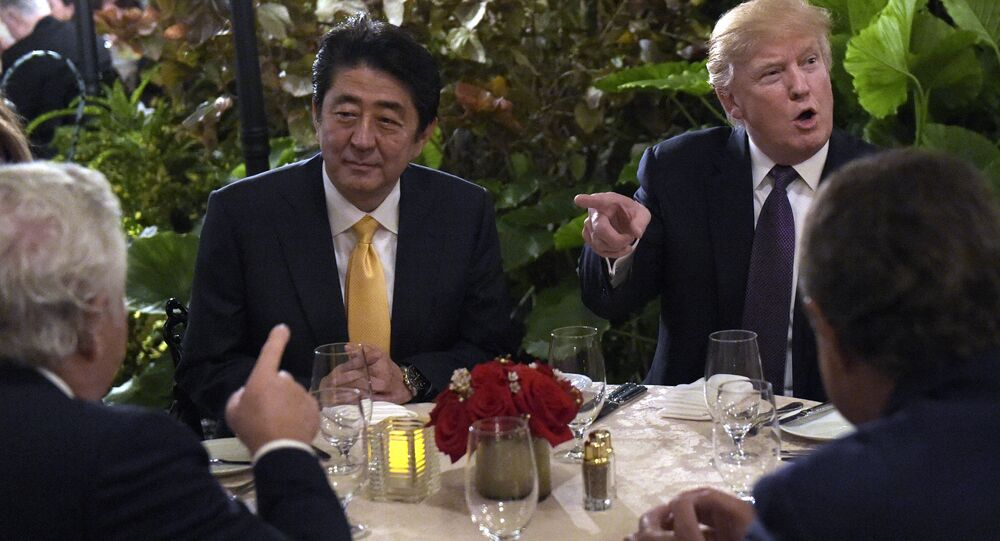President Donald Trump, second from right, sits down to dinner with Japanese Prime Minister Shinzo Abe, second from left, at Mar-a-Lago in Palm Beach, Fla., Friday, Feb. 10, 2017. Robert Kraft, owner of the New England Patriots, is at left. Trump is hosting Abe and his wife for the weekend.