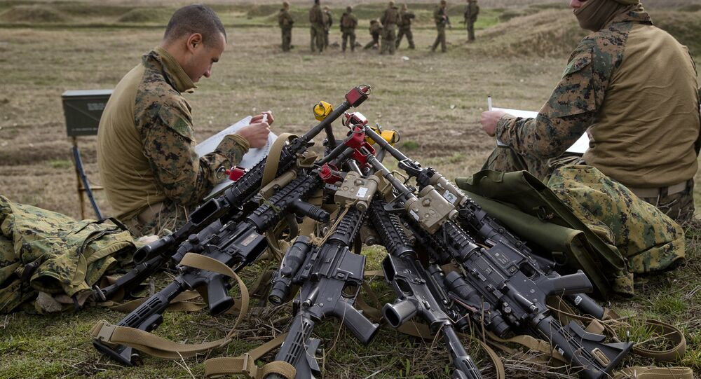 US Marines sit by a pile of assault rifles
