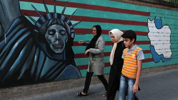 An Iranian family walks past anti-US graffiti on the wall of the former US embassy in Tehran on July 14, 2015 - Sputnik International