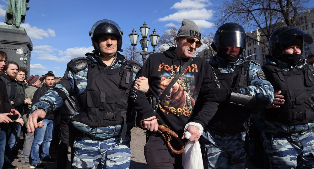 Police officers detain a participant in the unauthorized anti-corruption rally on Pushkinskaya Square in Moscow